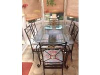 Wrought iron glass top dining table with 6 chairs.