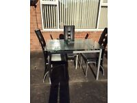 glass dining table and three chairs