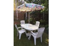 Garden table, 4 chairs and an umbrella for sale
