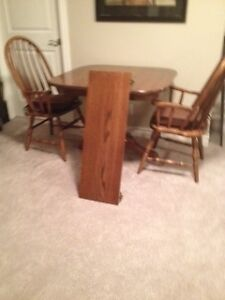 Solid oak pedestal table and two matching captains chairs