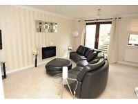 Black leather corner sofa and footstool