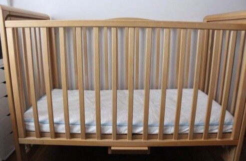 Cot bed with a sliding side.