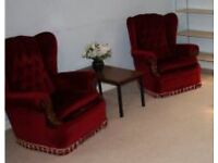 Two red wingback armchairs