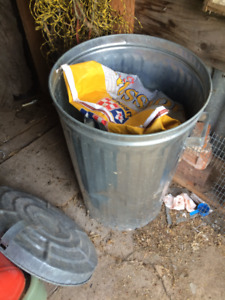 steel garbage can and unopened bag chick feed