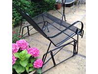 Black wrought iron glider bench