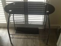 Small black glass table with silver legs.