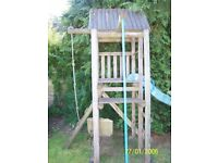 Climbing frame with slide, climbing wall, swing rope, platform with roof over and ladders.