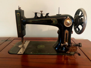 Antique Reliance sewing machine in stand