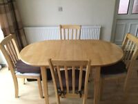 Kitchen table and four matching upholstered chairs in cream.