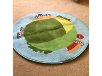 A circular mat, that has a farm scene
