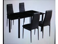 Black glass table with four chairs