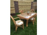 Cane table with glass top and 4 chairs