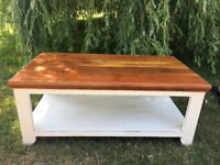 Coffee table with exposed wood top and painted legs