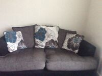 2 x 2 seater sofas. Modern grey and black with a blue flower on scatter cushions.