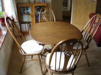 ERCOL CHESTER DINING TABLE AND FOUR SWAN BACK CHAIRS.