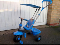 Blue first tricycle with belt, push handle, and sun roof