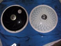 Two retro circular flourescent glass lights, one black glass, one white glass.