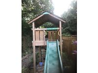 Wooden climbing frame with slide and sand pit