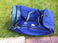 Blue/green wheeled travel bag.