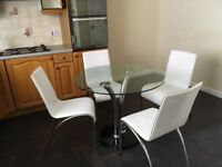 Glass kitchen table and white chairs