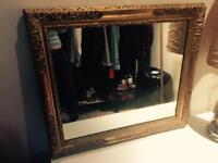 Big mirror with gold frame.