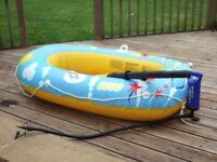 Small inflatable dinghy with oars and other beach toys