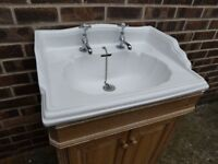 Bathroom sink cabinet made of Oak with traditional ceramic basin and hot and cold chrome taps