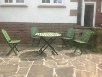 Attractive small round table with four chairs in green painted slatted wood