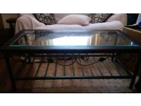 Heavy metal based coffee table with leaf design on sides top is wood with inlaid glass
