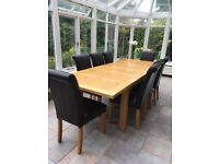 Extendable oak dining table with 8 brown leather chairs