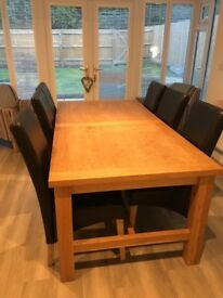 Solid oak extending table and 6 dark brown faux leather chairs