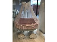 White wicker crib with wheels and pink or white bedding and drapes