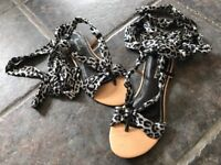 brand new boxed womens white and black leopard print sandals with tie ribbon around ankle and calf.