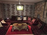Set includes sofas, curtains, table, cushions, 2 coffee tables and 3 tan floral decorations, red rug