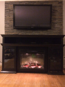 Dark wood fireplace mantle with glass doors