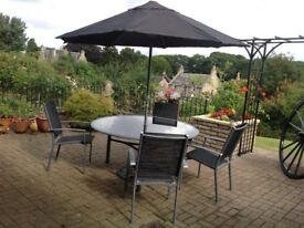 Garden table with black glass top and 4 chairs along with sun umberlla and stand