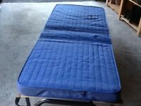 Blue folding single bed with protective cover. Castors for easy movement. Very good condition.