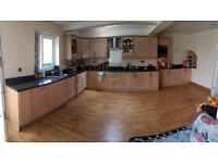 Second hand kitchen in wood with black granite worktops.