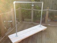 Wood and metal industrial clothes rail on castors