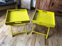 A pair of stylish folding habitat bedside tables