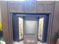Antique black cast iron fireplace with tiled insert, copper canopy & wooden engraved surround