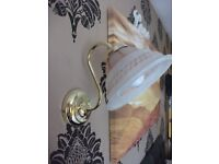 Gold wall light with glass shade
