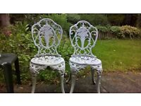 Two cast aluminium chairs, painted white.