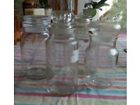 Four different size glass storage jars. Two have decorative stoppers and all seal very well.