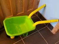 Child's green plastic wheelbarrow