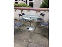 GLASS TOP DINING TABLE with 4 foldaway chairs.