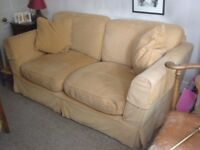 large two-seater sofa with gold loose covers. East Oxford collection only