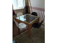 Square wooden legged glass topped table, and 4 chairs.