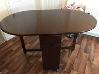 Dark wood folding dining set with 4 chairs.