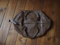 Tan leather travel bag with zip top and two handles